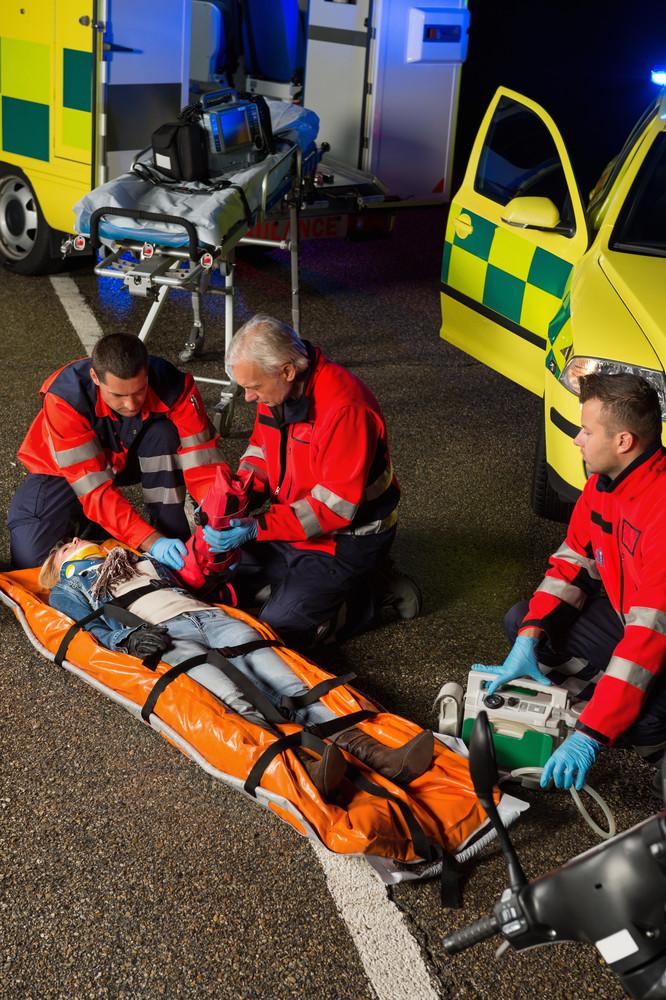 Paramedics assisting injured woman motorbike driver on stretcher at night
