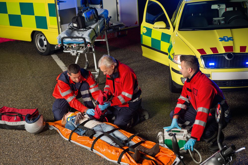 Paramedics helping injured woman motorbike driver on stretcher at night