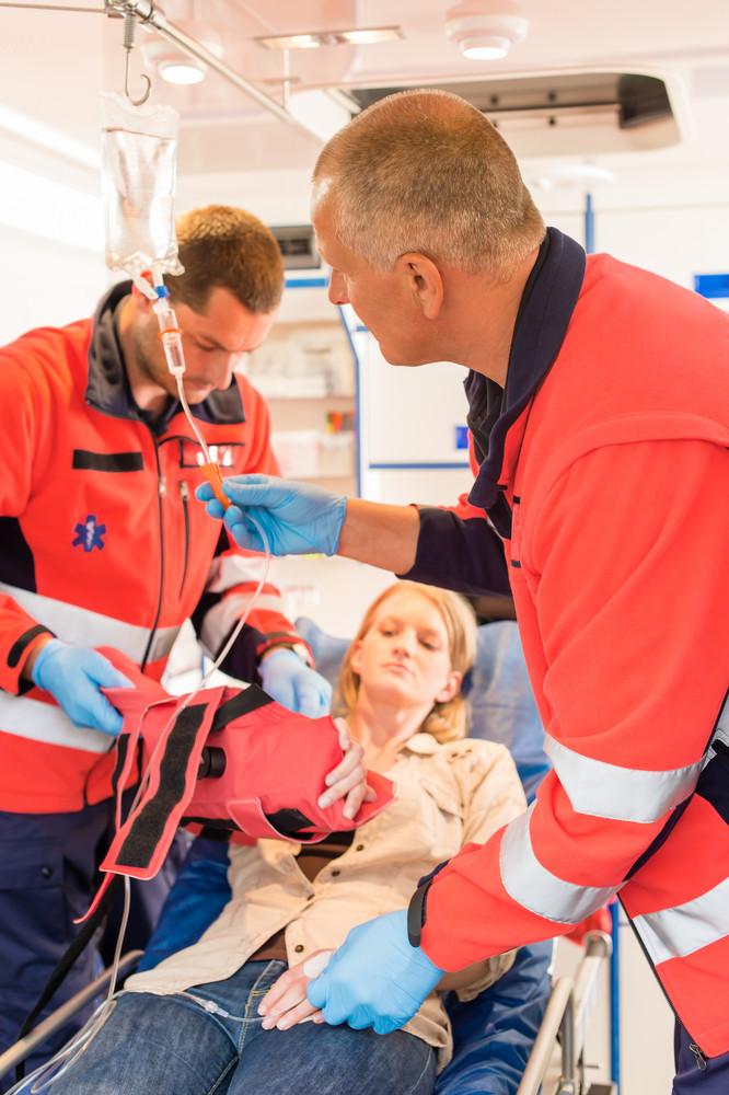 Paramedics in ambulance treating patient broken arm emergency intervention