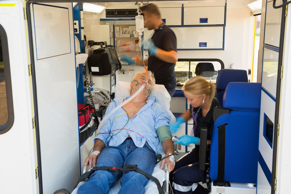 Paramedics treating unconscious elderly man on stretcher in ambulance car