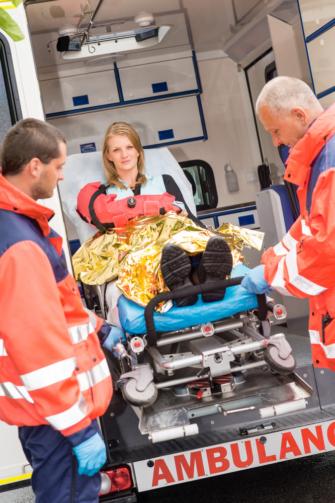 Paramedics with injured woman on stretcher in ambulance helping accident