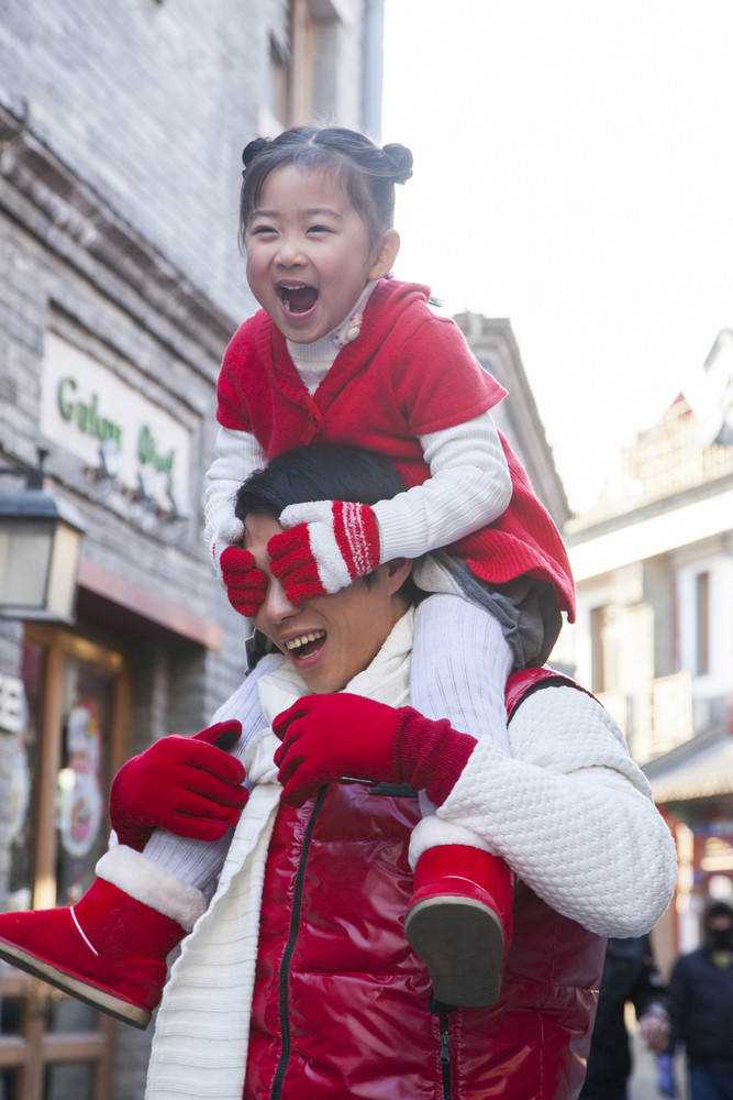 Parent carrying child on shoulders dressed in holiday attire