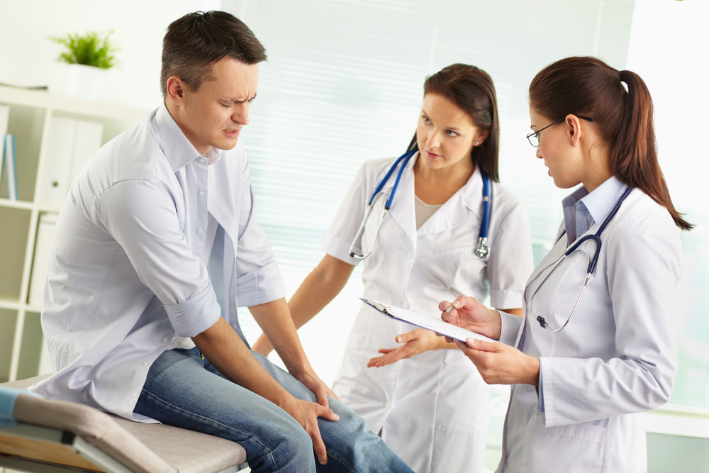 Paciente que sofre de dor na perna sendo examinada por uma médica do sexo feminino e seu assistente