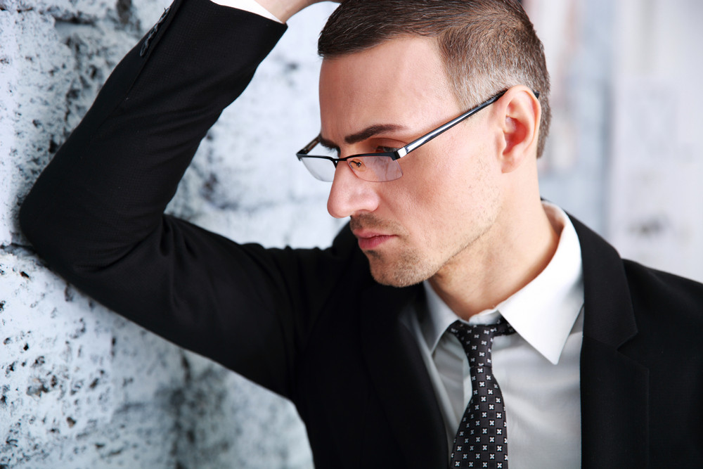 Pensive businessman in glasses leaning on a brick wall