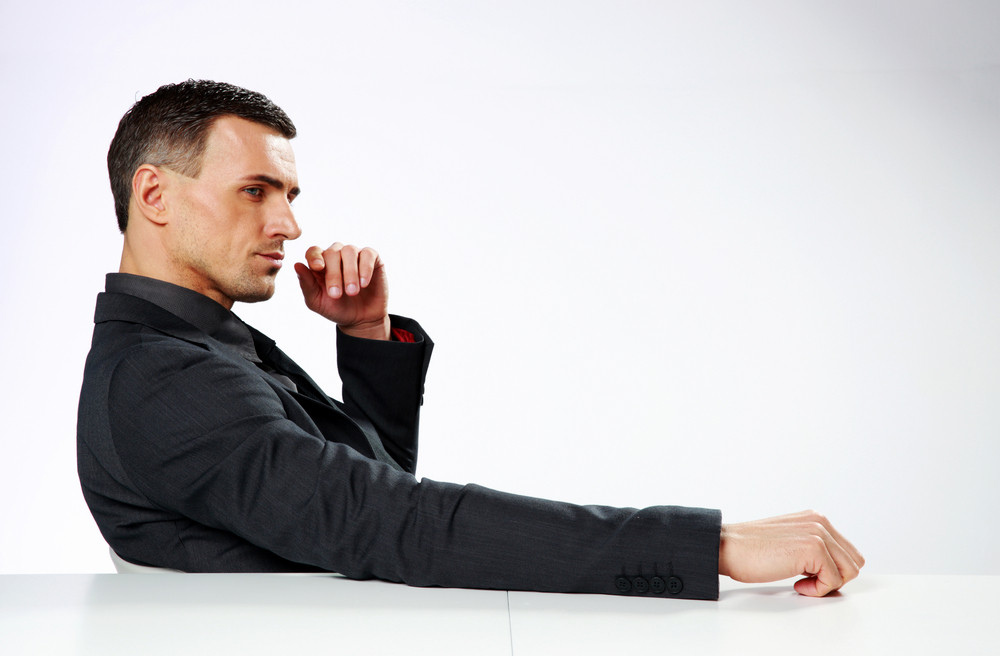 Pensive businessman sitting at his workplace and looking away isolated on white background