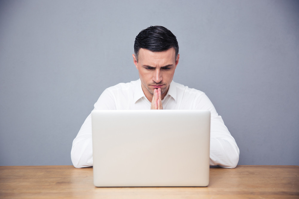 Pensive businessman sitting at the table and using laptop