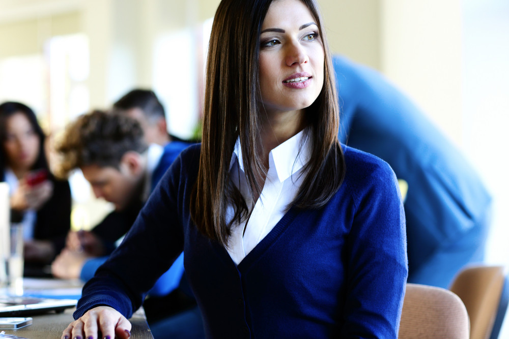 Pensive businesswoman sitting at the table with colleagues on background