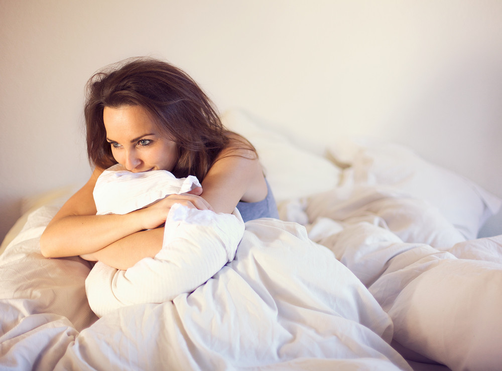 Pensive woman smiling and sitting alone on bed thinking of someone