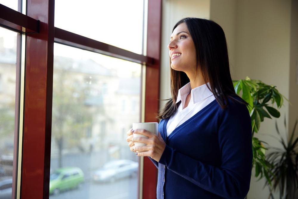 Pensive young businesswoman standing with cup of coffee in office