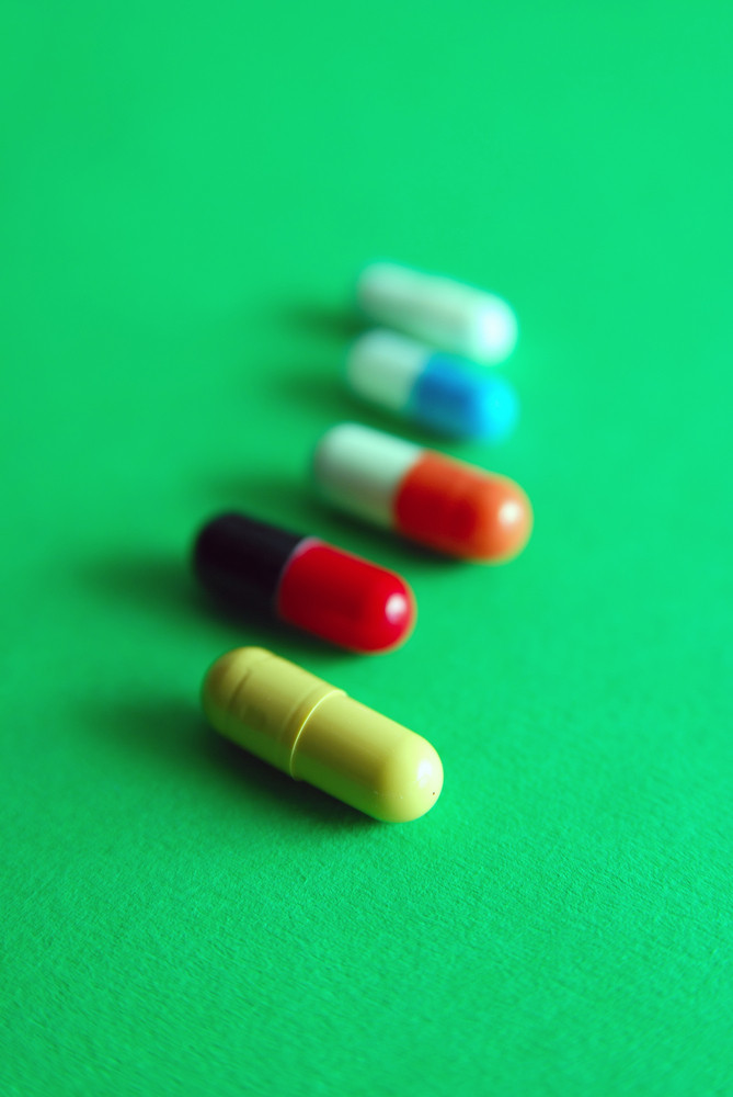 Pills on green background in row