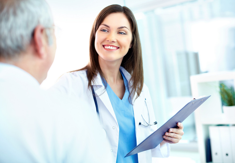 Portrait of young pretty assistant looking at clinician while interacting with him