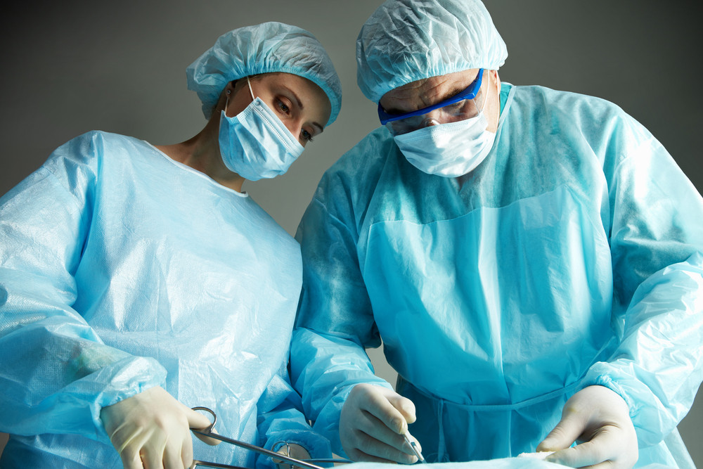 senior doctor operating and a nurse standing with a clamp royalty