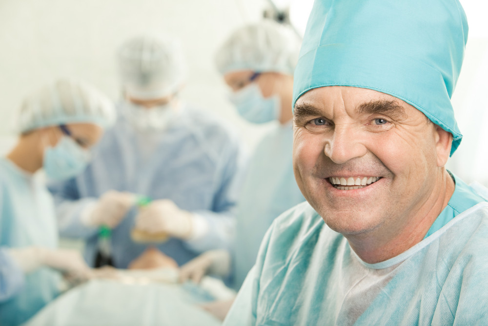 Portrait of happy doctor on background of working surgeons