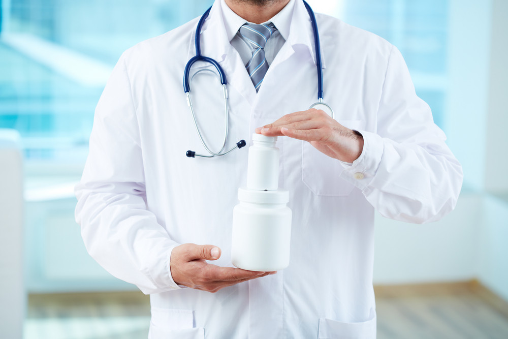 Close-up of doctor holding two containers with vitamins