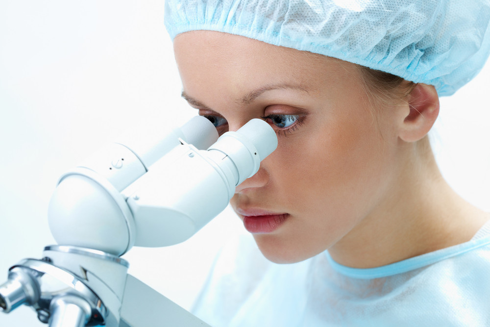 Portrait of medical student looking through microscope in laboratory