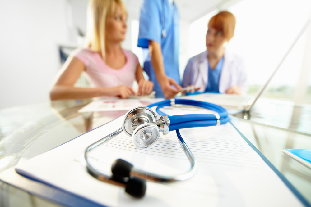Close-up of stethoscope and paper on background of doctors and patient communicating