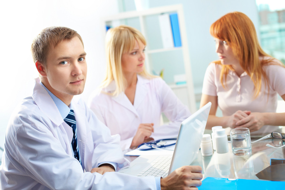Portrait of confident male doctor looking at camera in working environment