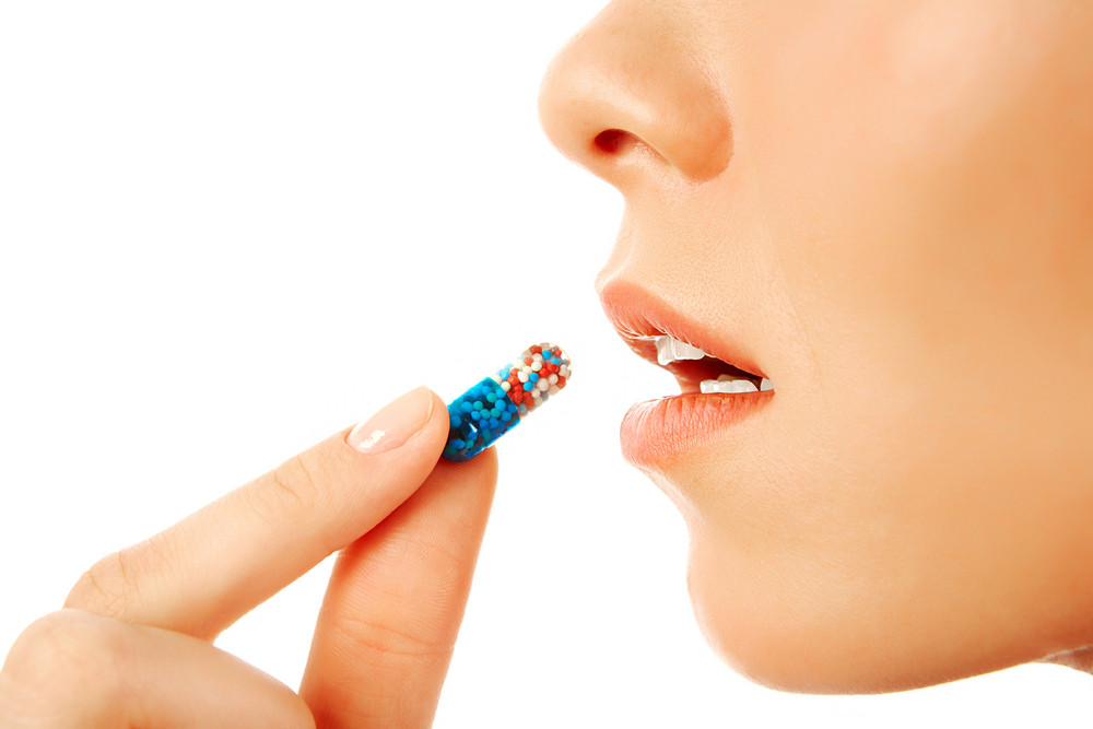 Profile of young woman holding pill by her mouth before taking it