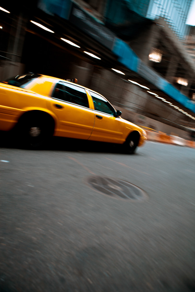 Pnned motion blur of a city street scene with a yellow taxi cab speeding by.