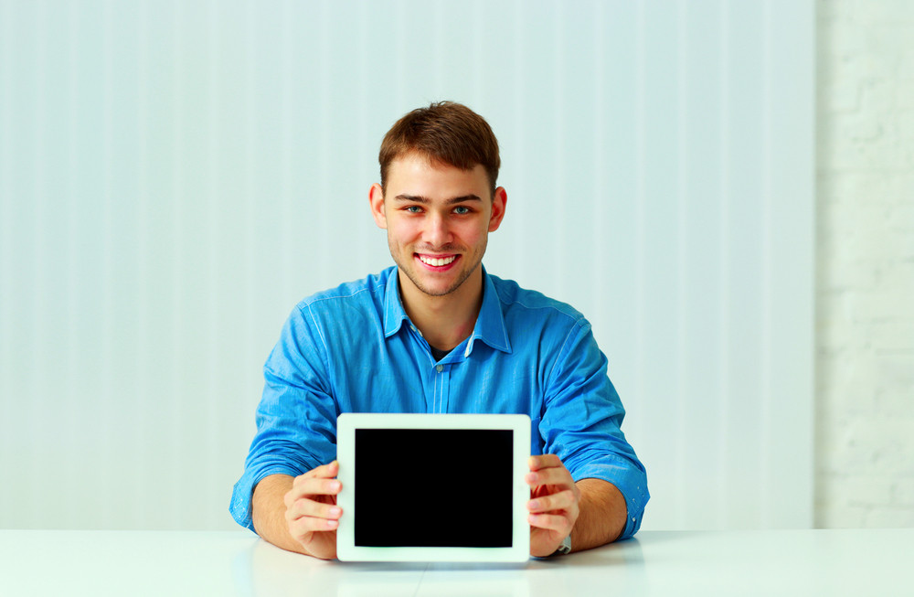 Portait of a young businessman shows the tablet computer display at office