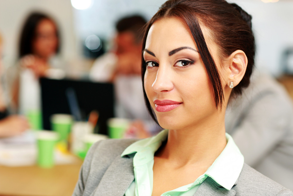 Portrait of a beautiful businesswoman in front of colleagues