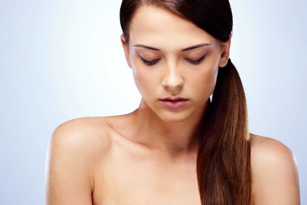 Portrait of a beautiful woman with closed eyes on blue background