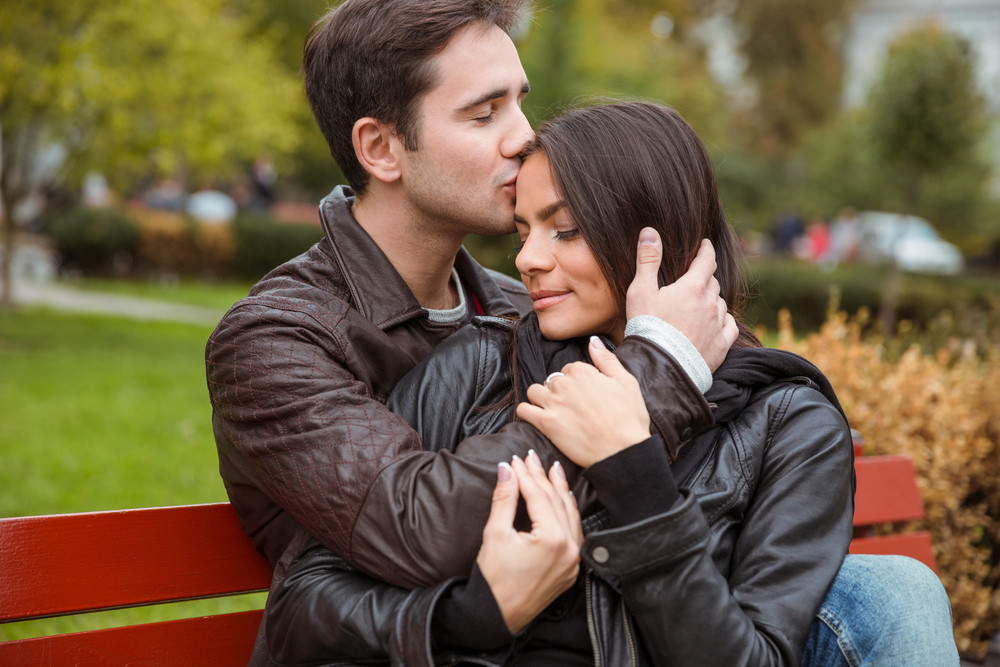 Portrait of a beautiful young couple hugging outdoors on the bench