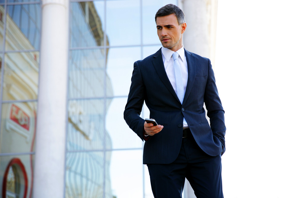 Portrait of a businessman standing and holding smartphone on the street