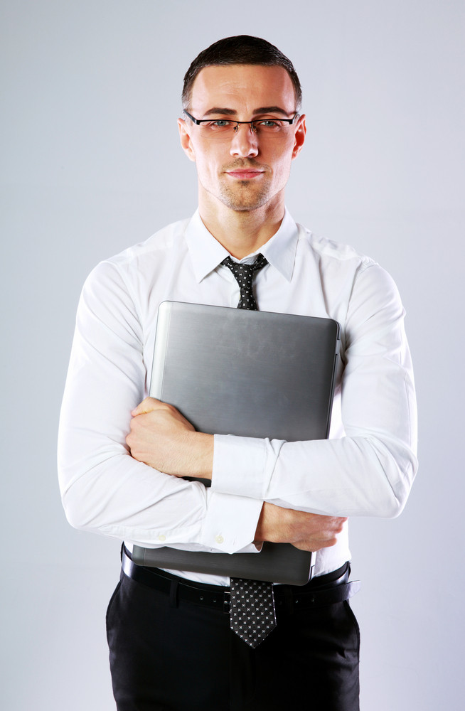 Portrait of a businessman with laptop on gray background