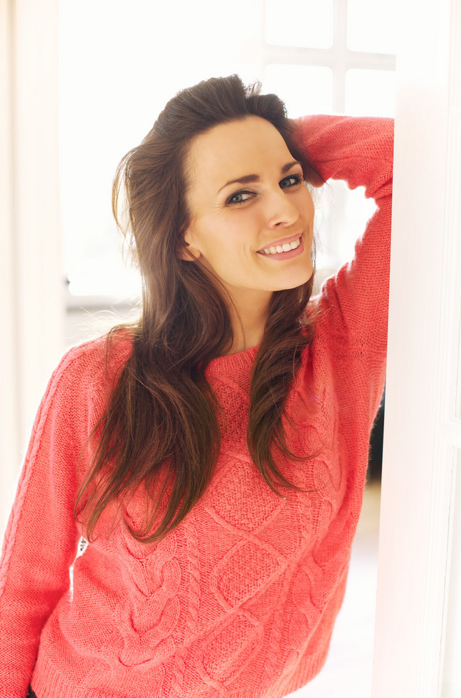 Portrait of a charming woman posing beside the door looking at you