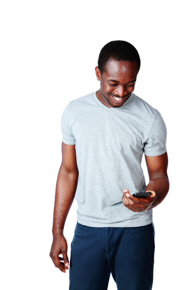 Portrait of a cheerful african man using smartphone over white background
