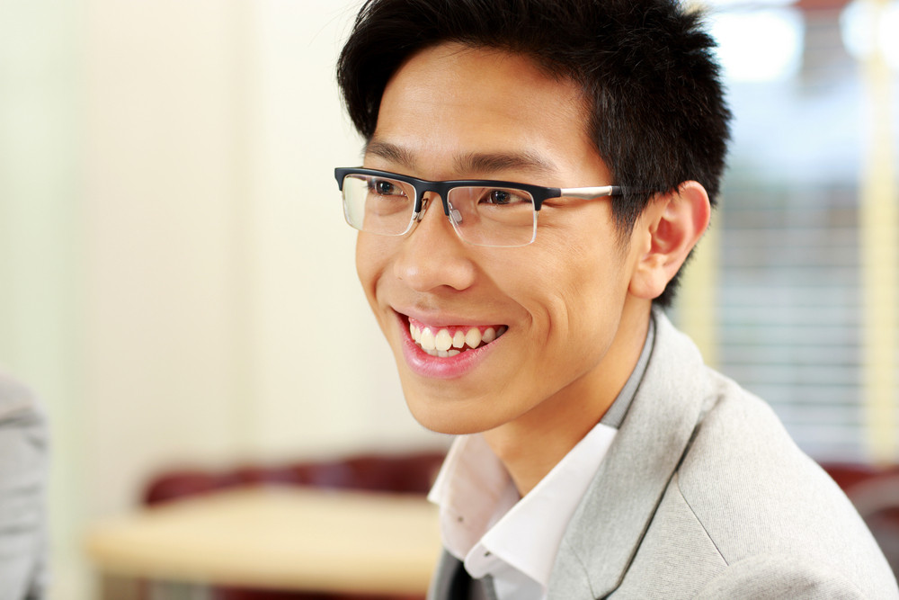 Portrait of a cheerful businessman in glasses at office