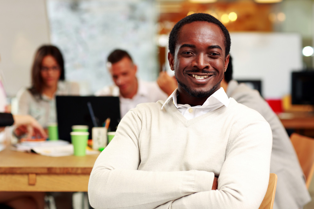 Portrait of a cheerful businessman sitting in front of colleagues