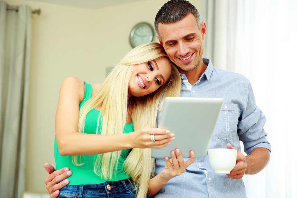 Portrait of a cheerful couple with tablet computer and cup of coffee