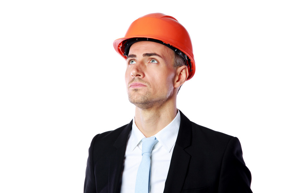 Portrait of a confident businessman in helmet looking up over white background