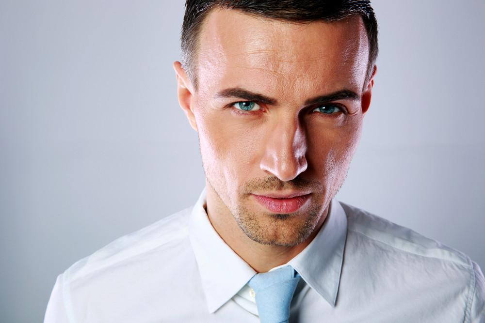 Portrait of a confident businessman on gray background