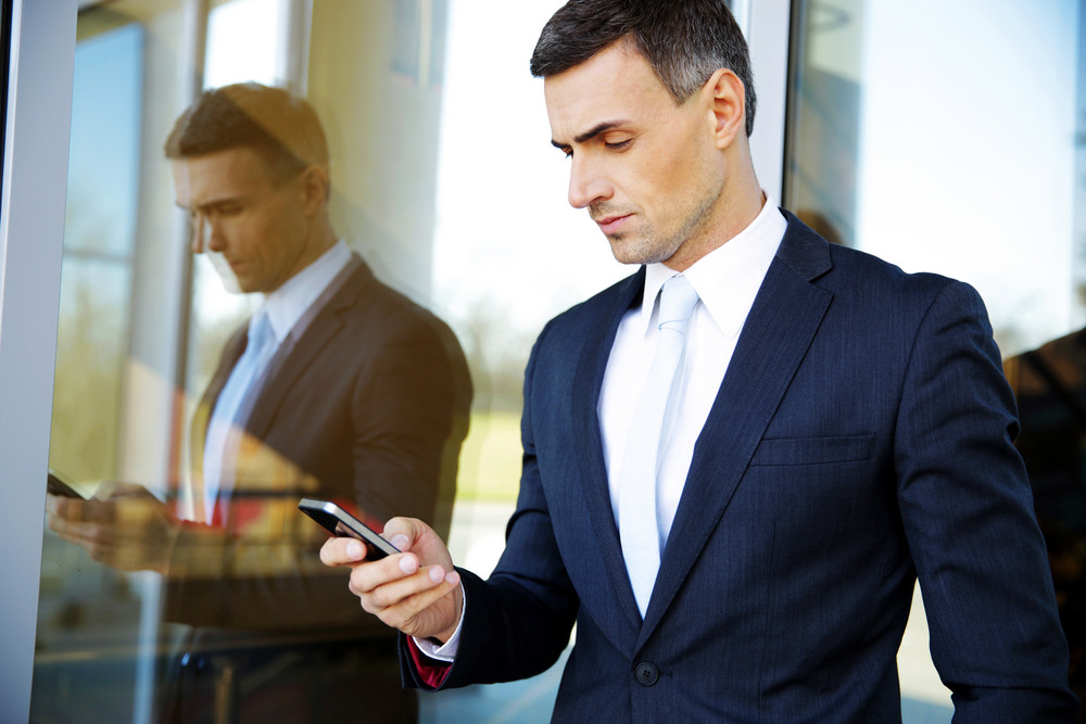Portrait of a confident businessman using smartphone
