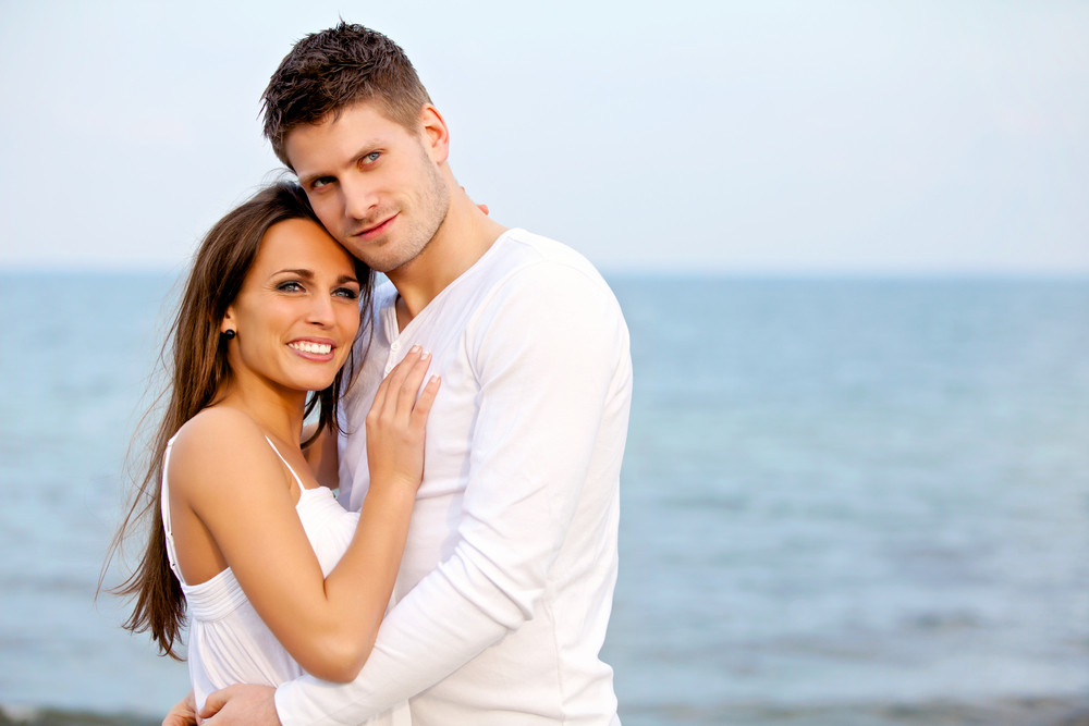 Portrait of a couple posing with the beach as background