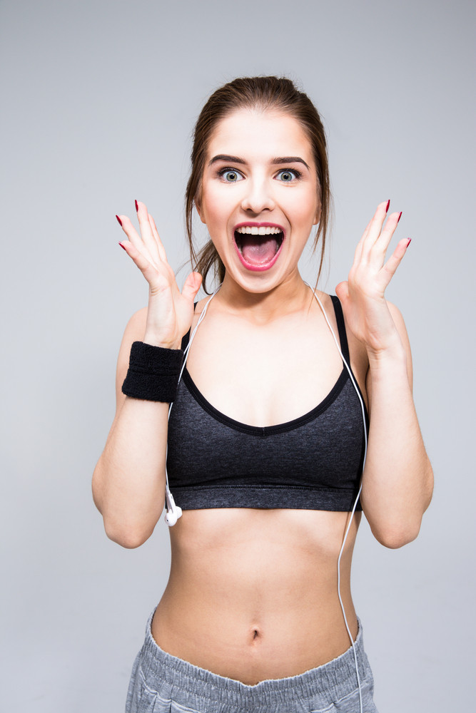 Portrait of a crazy sports woman over gray background