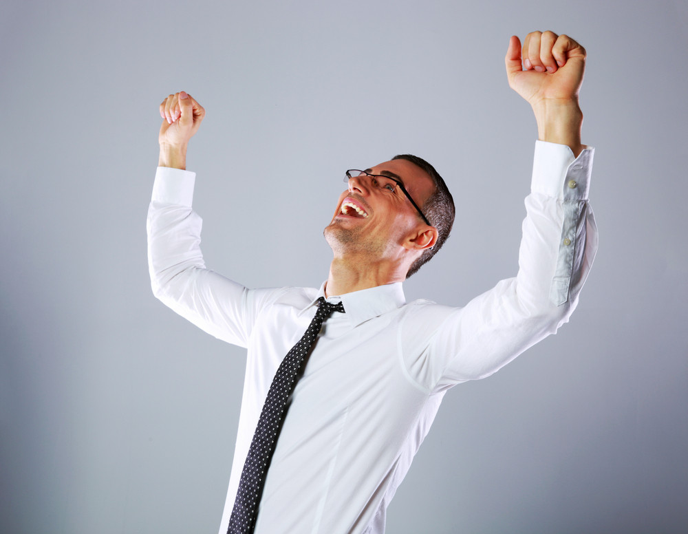 Portrait of a excited businessman on gray background