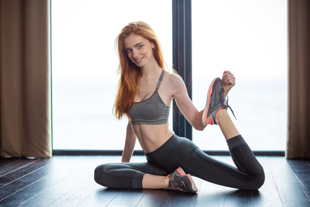 Portrait of a fitness redhair woman stretching legs