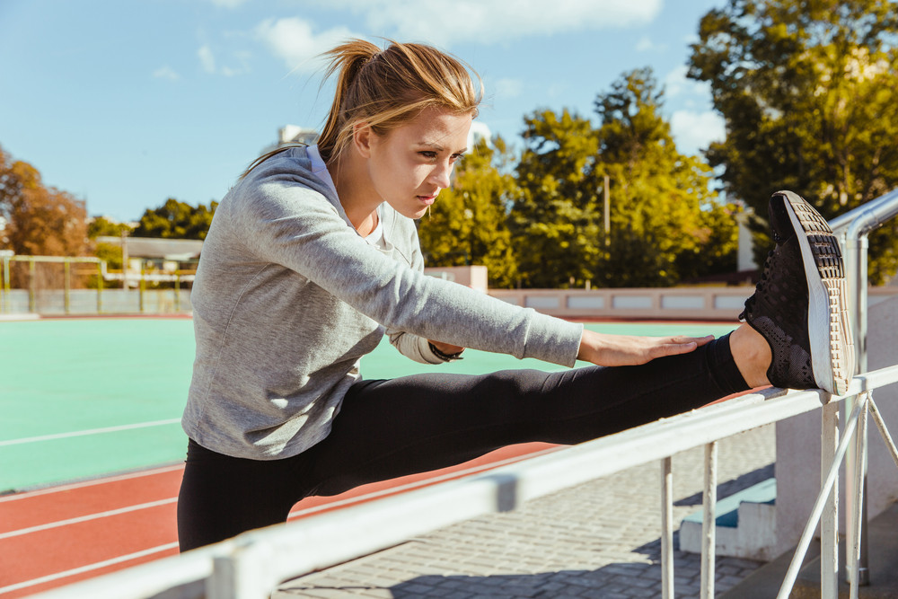 Portrait of a fitness woman stretching legs on outdoor stadium