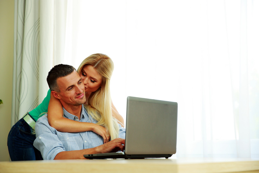 Portrait of a girl kissing her boyfriend while he using laptop