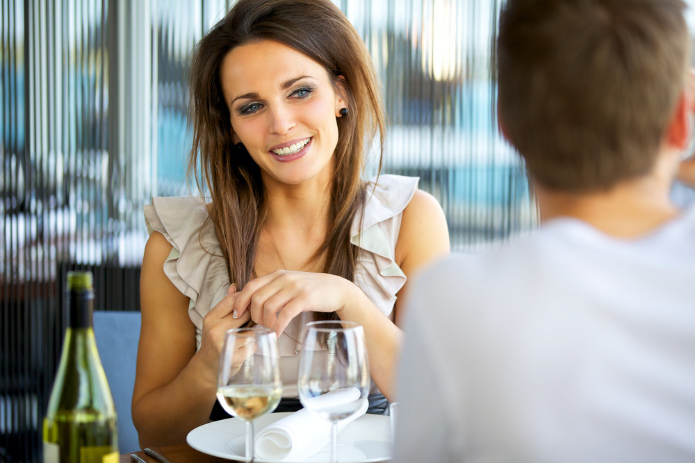 Portrait of a gorgeous woman smiling at her date while holding her hair