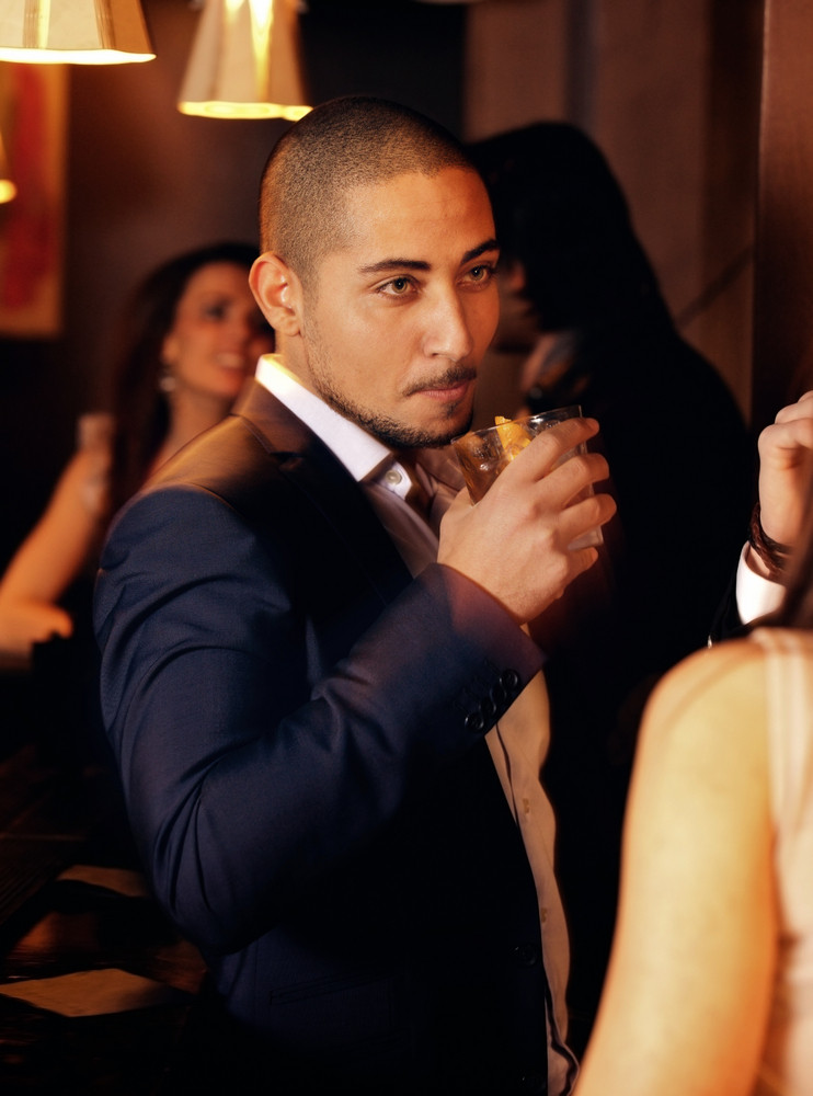 Portrait of a guy at a party holding a glass of whiskey