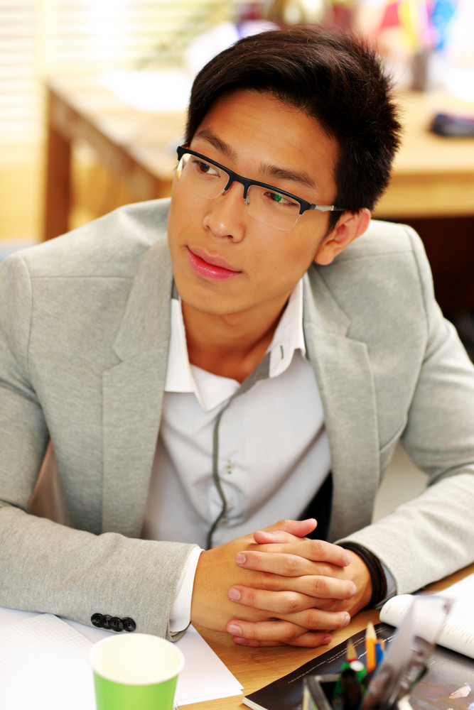 Portrait of a handsome asian man in glasses at office
