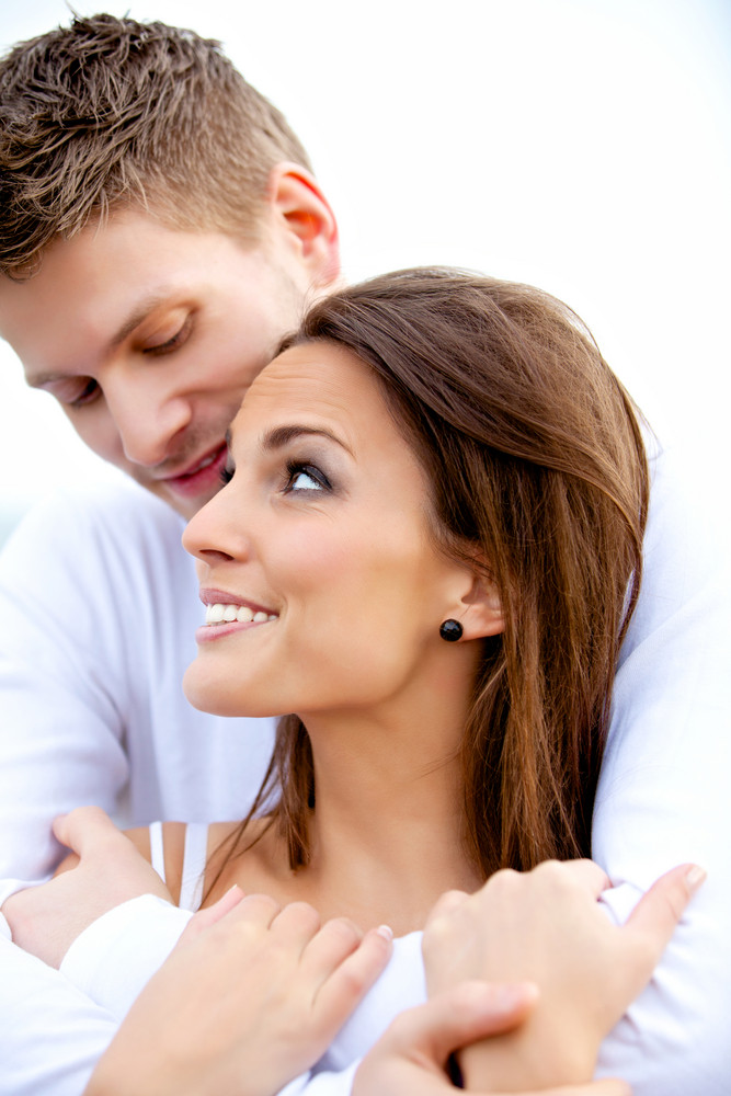 Portrait of a handsome boyfriend hugging his beautiful girlfriend isolated on white
