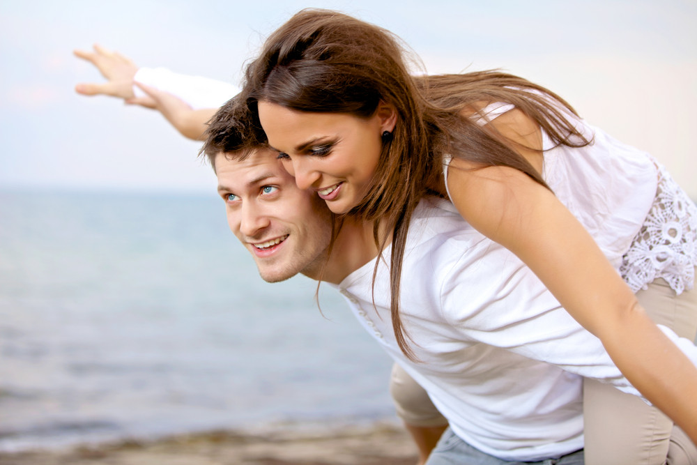Portrait of a handsome guy carrying his girlfriend on his back against a bright background