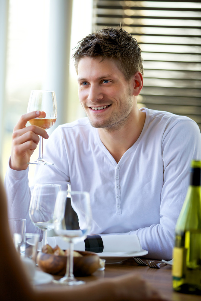Portrait of a handsome guy holding a glass of wine at a restaurant