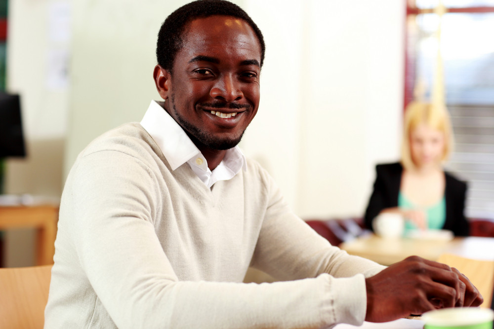 Portrait of a happy african man sitting at the table in office